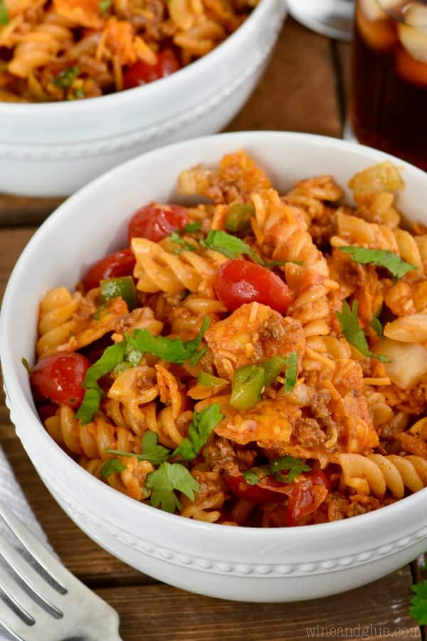 In a small white bowl, the Taco Pasta salad has different shades of red from the halved cherry tomatoes and red sauce.
