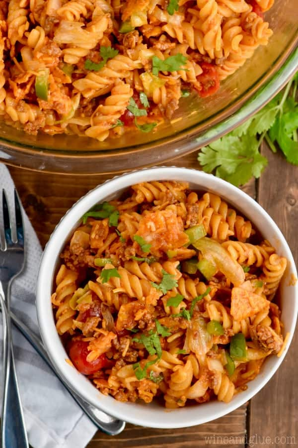 In a small white bowl, the Taco Pasta Salad is mixed together, but you can see the individual ingredients of ground beef, lettuce, green peppers, cherry tomatoes, pasta, and onion.