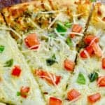 Overhead close up image of pesto pizza garnished with parmesan, basil and tomato