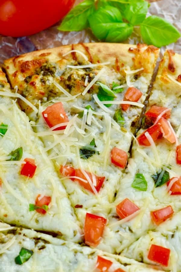 up close view of easy pesto pizza recipe garnished with cheese and tomatoes