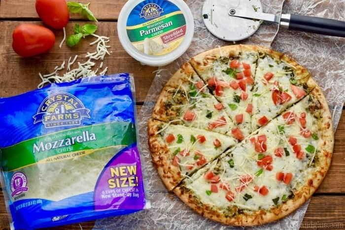 overhead view of pesto pizza recipe and the ingredients needed to make it