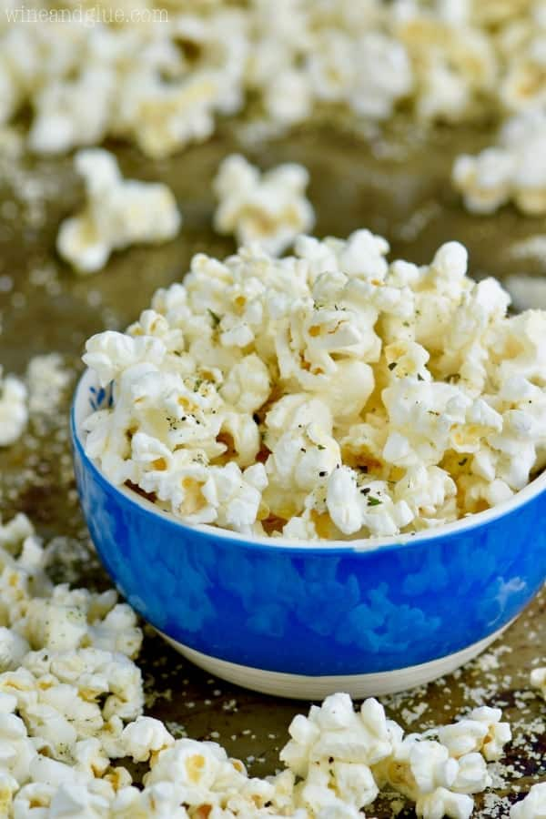 In a blue bowl, the Italian Popcorn has dry basil and dry parsley.
