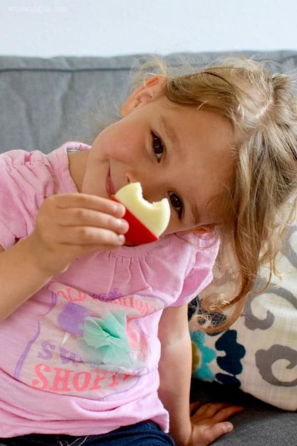 A little girl holding a small Babybel's Mini Cheese with a small bite.