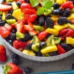 pinterst graphic of fruit salad in a bowl that is topped with a mint leaf sprig