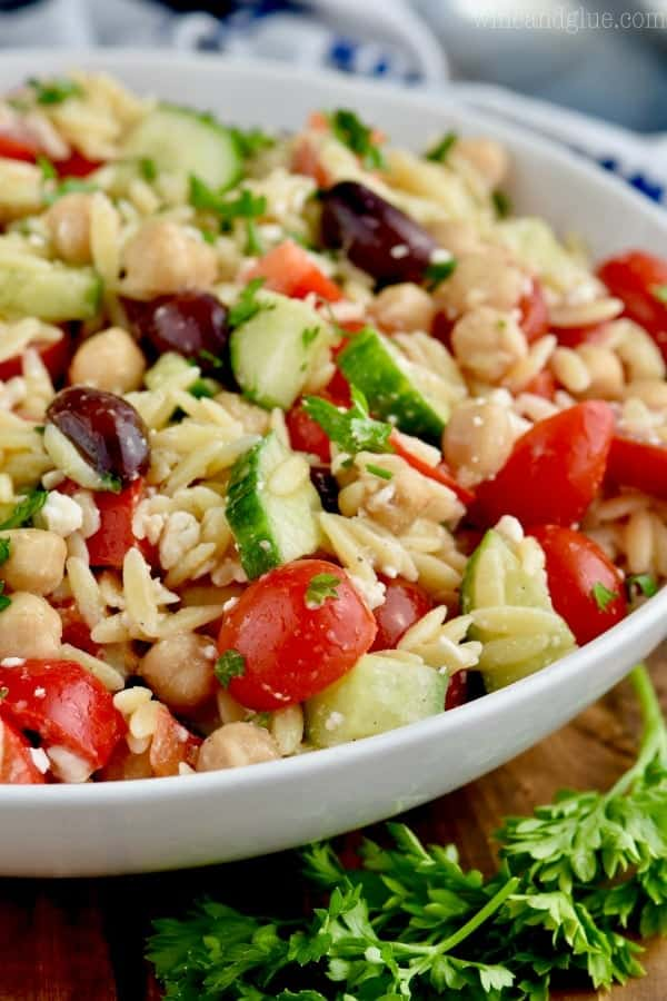 The Easy Orzo Pasta Salad has sliced cherry tomatoes, olives, and sliced cucumbers.