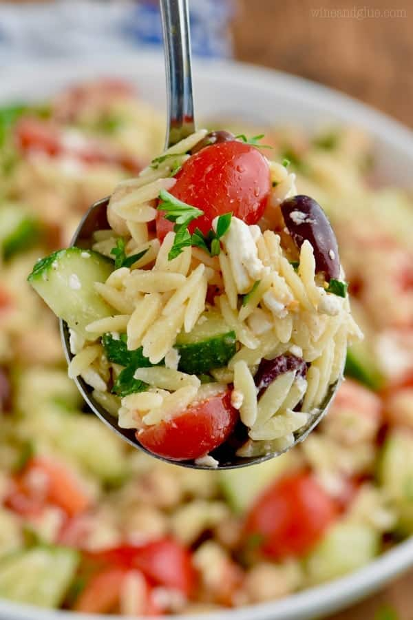 A spoonful of the Easy Orzo Pasta salad showing the rainbow colors of the cherry tomatoes, orzo, olives, and cucumbers