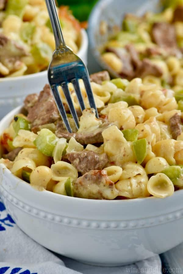 In a small bowl, the Philly Cheesesteak Mac and Cheese has orecchiette pasta, chunked steak, and cubed green peppers.