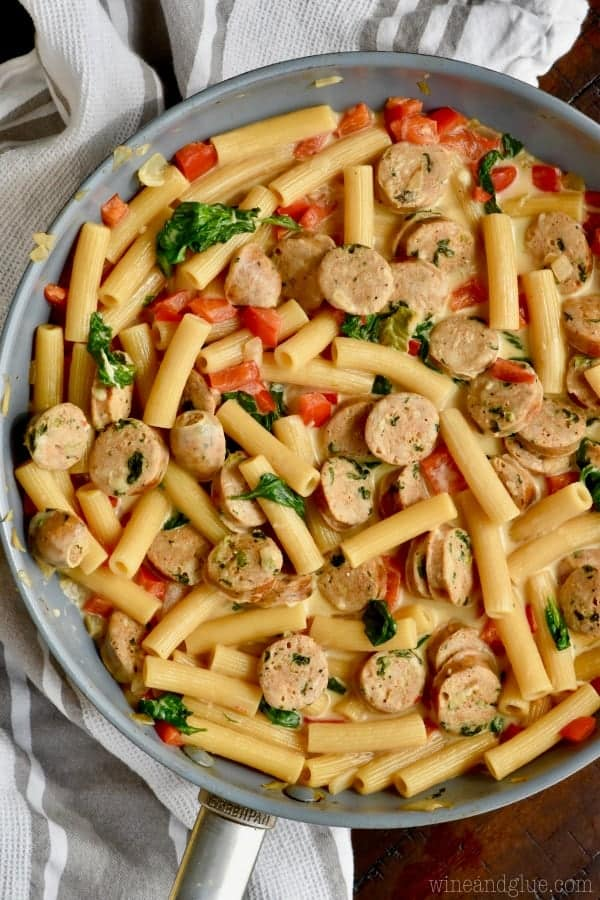 In a skillet, the Sausage Pasta Skillet shows the different rainbow colors from the sausage, pasta, spinach, red peppers, and tomatoes.