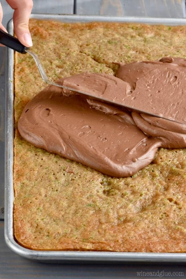 Spreading chocolate frosting on zucchini cake.