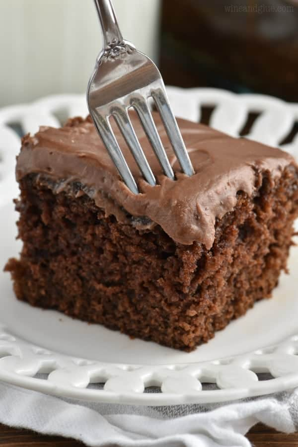 A fork is digging into the Chocolate Snack Cake that has a very moist and spongy cake layer with chocolate frosting.