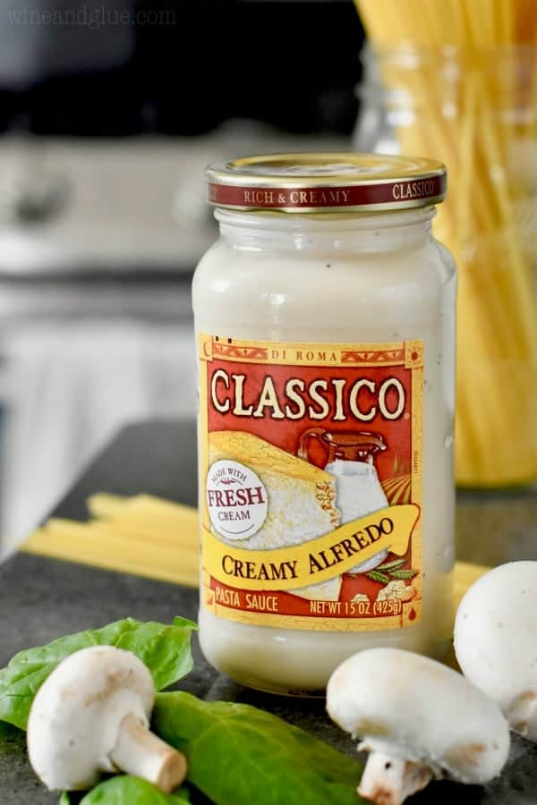 A bottle of Clssico's Creamy Alfredo is behind some white button mushroom and spinach