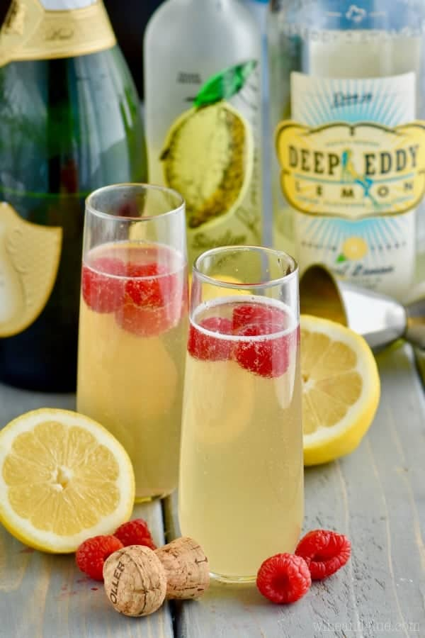 In a champagne fluke, the Lemon Champagne Cocktail has a yellow tint and topped with raspberries