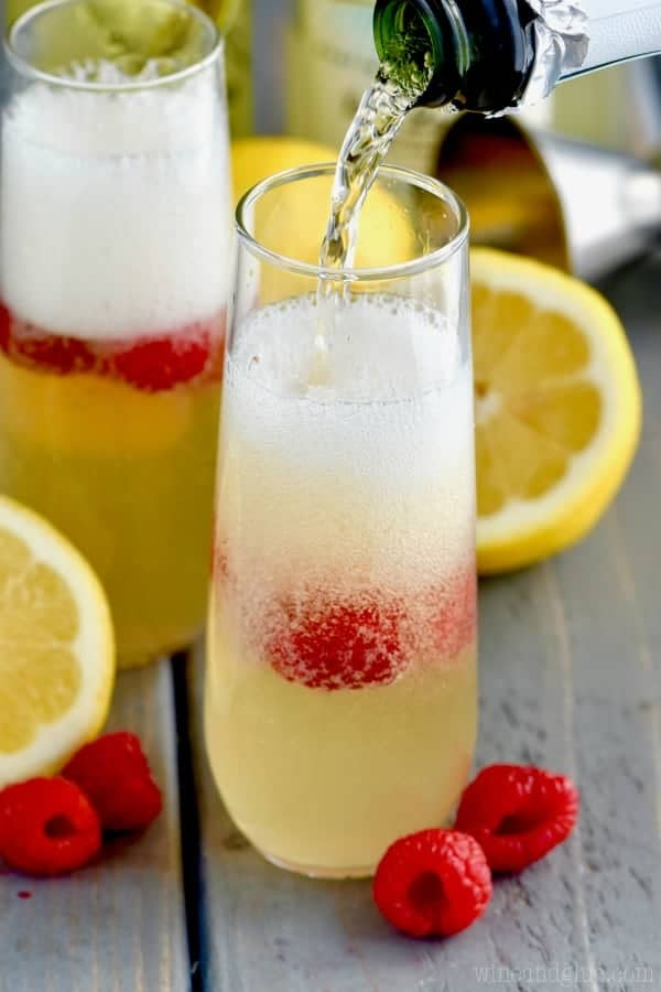 Champagne is being poured into the Lemon Champagne Cocktail which has raspberries