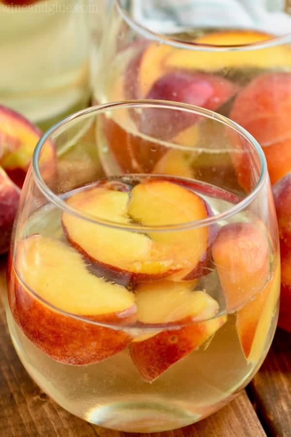 wine glass filled with peach sangria recipe including fresh peaches