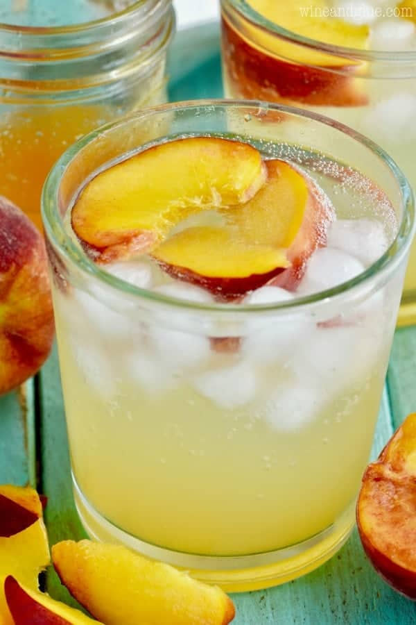 In a clear glass, the Peach Vodka Smash has two sliced peaches with ice.