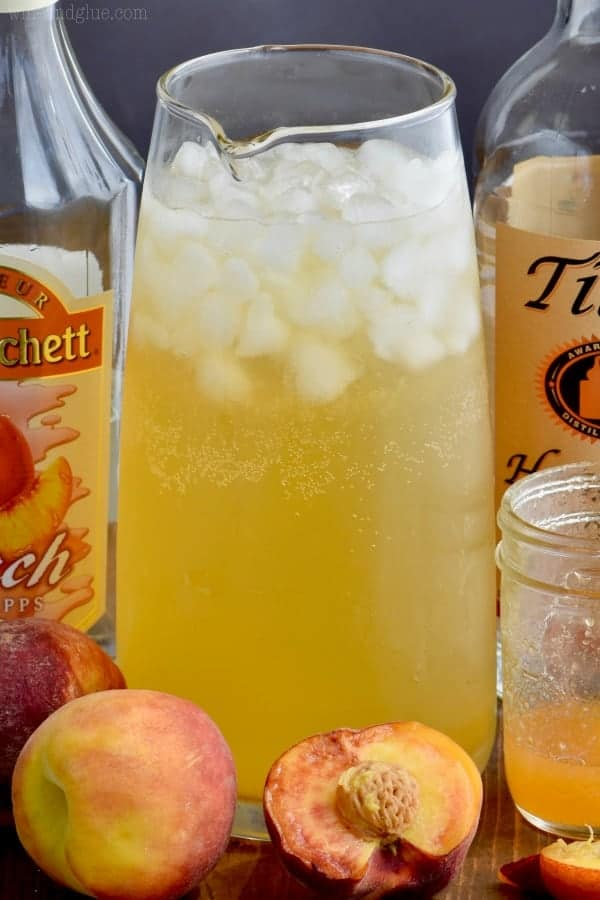 In a large glass pitcher, the Peach Vodka Smash has a golden yellow color with ice cubes.