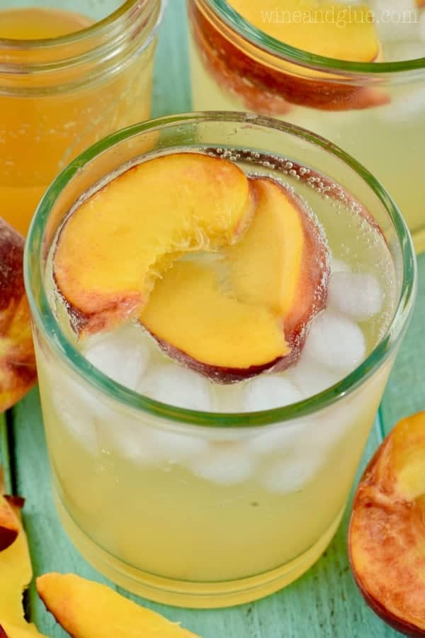 An overhead photo of the glass of the Peach Vodka Smash with three slices of peach and ice cubes.