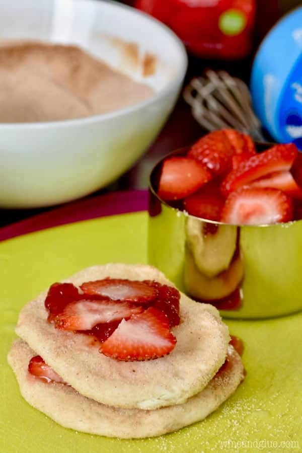A stack of biscuit dough has sliced strawberries in-between the dough and some sugar