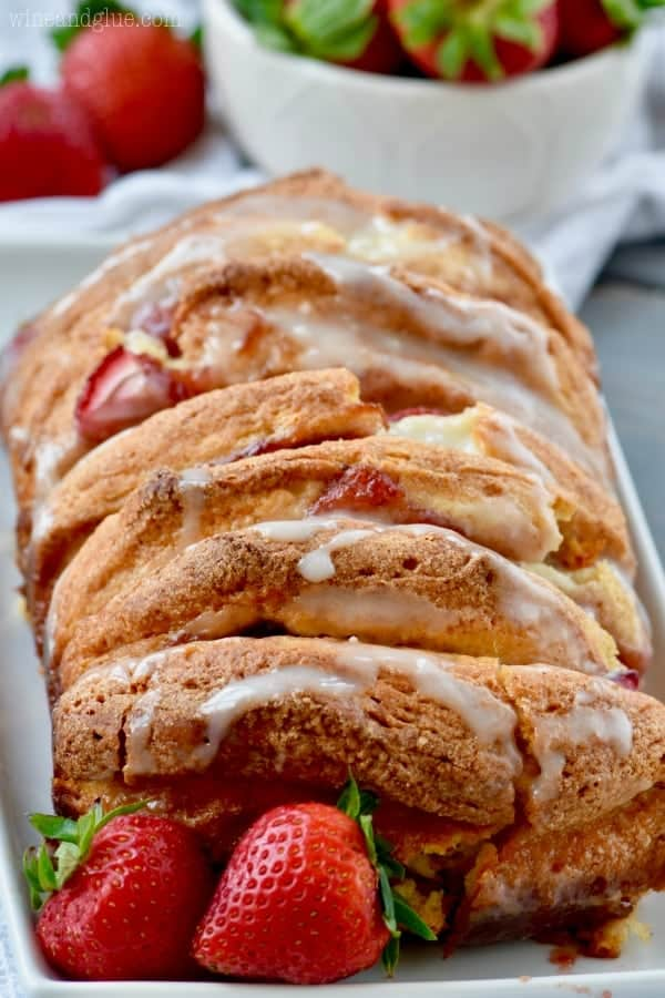On a white rectangular plate with strawberries on the side, the Strawberries and Cream Pull Apart Bread has a beautiful golden brown crust with white icing on top.