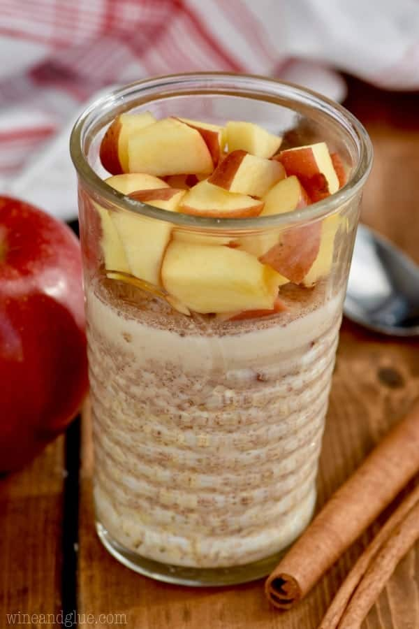 In a clear glass, the Apple Cinnamon Overnight oats is topped with sliced red apples and sprinkled with cinnamon