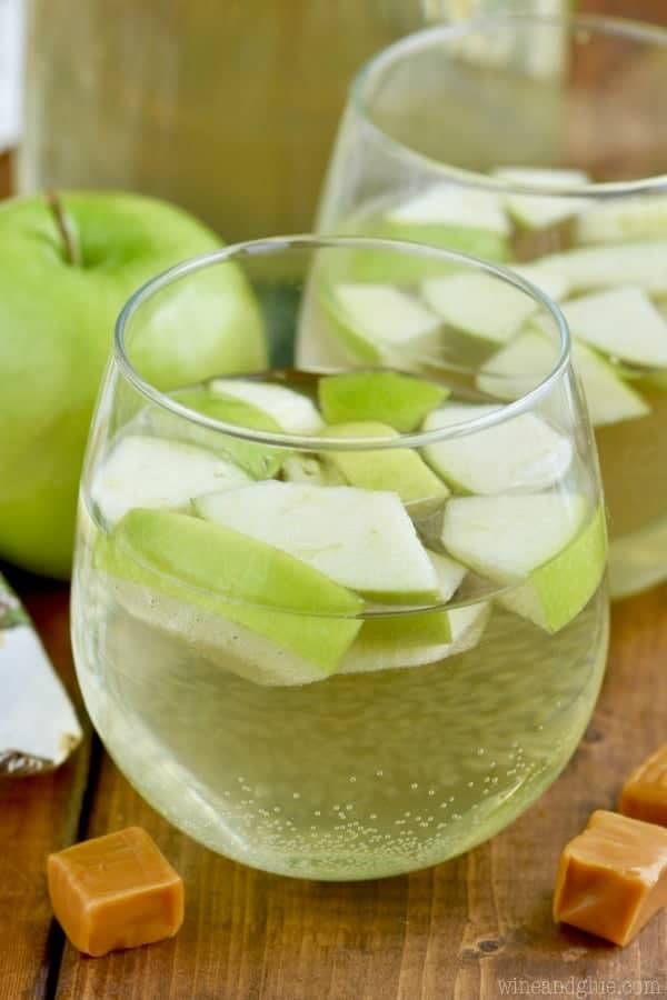 In a glass, the Caramel Apple Sangria has sliced green apple slices.