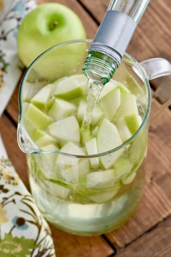 In a large glass pitcher, white wine is being poured on top of sliced green apples.