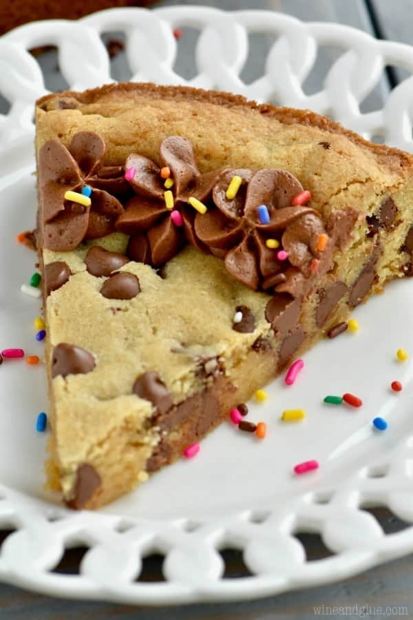 On a white plate, there is a slice of the Chocolate Chip Cookie Cake with chocolate frosting on the edge and rainbow sprinkles.