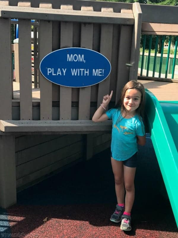 """A little girl pointing at a sign in the park that says, """"Mom, play with me!"""""""