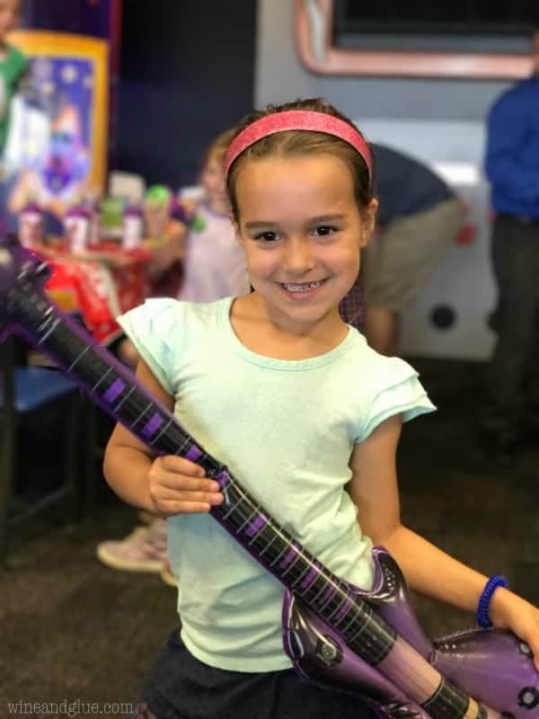 A little girl with a headband holding an inflatable guitar.