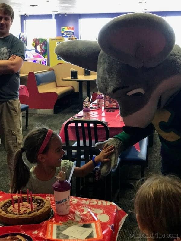 A little girl is giving Chuck E. Cheese a high-five