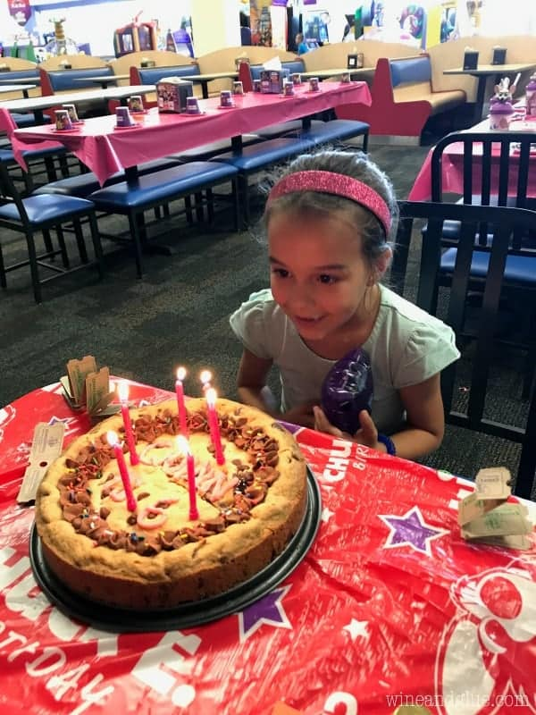 A little girl about to blow the candles on the cookie cake.