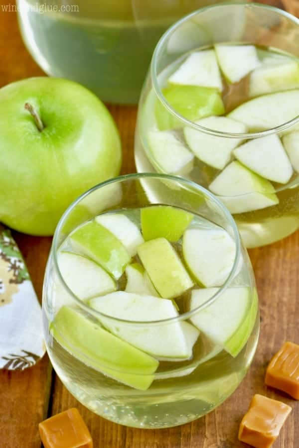 An overhead photo of two glasses filled with the Caramel Apple Sangria and sliced green apples.