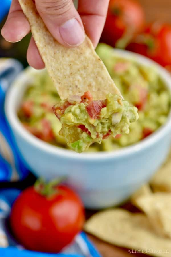 On a tortilla chips, the Mom's Amazing Guacamole has tomato red speckles within the green avocado.