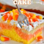 piece of candy corn poke cake, the colors of candy corn with cool whip on top and topped with candy corn