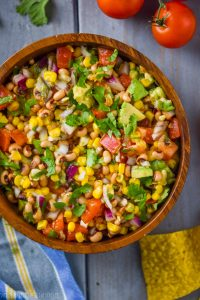 overhead view of a wood bowl on a blue wood surface surrounded by tomatoes and chips and with cowboy caviar inside