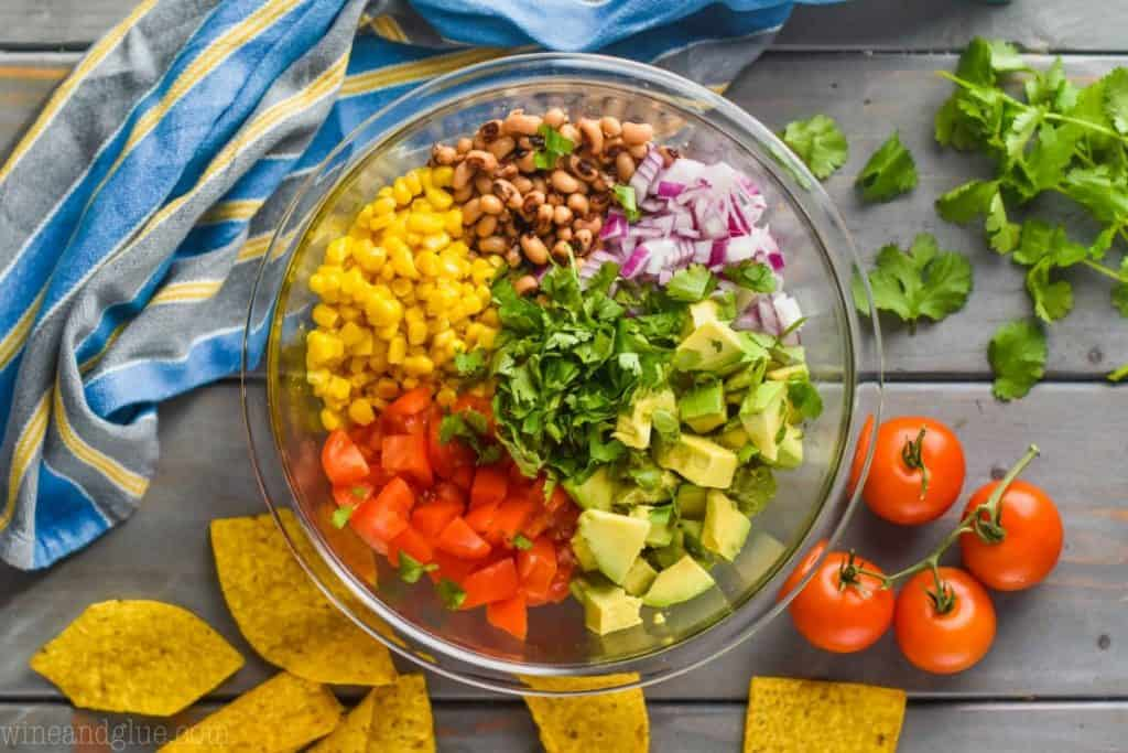 overhead view of a clear bowl that is full of the ingredients for cowboy caviar dip, around the bowl is tortilla chips, tomatoes on the vine, cilantro and a striped towel