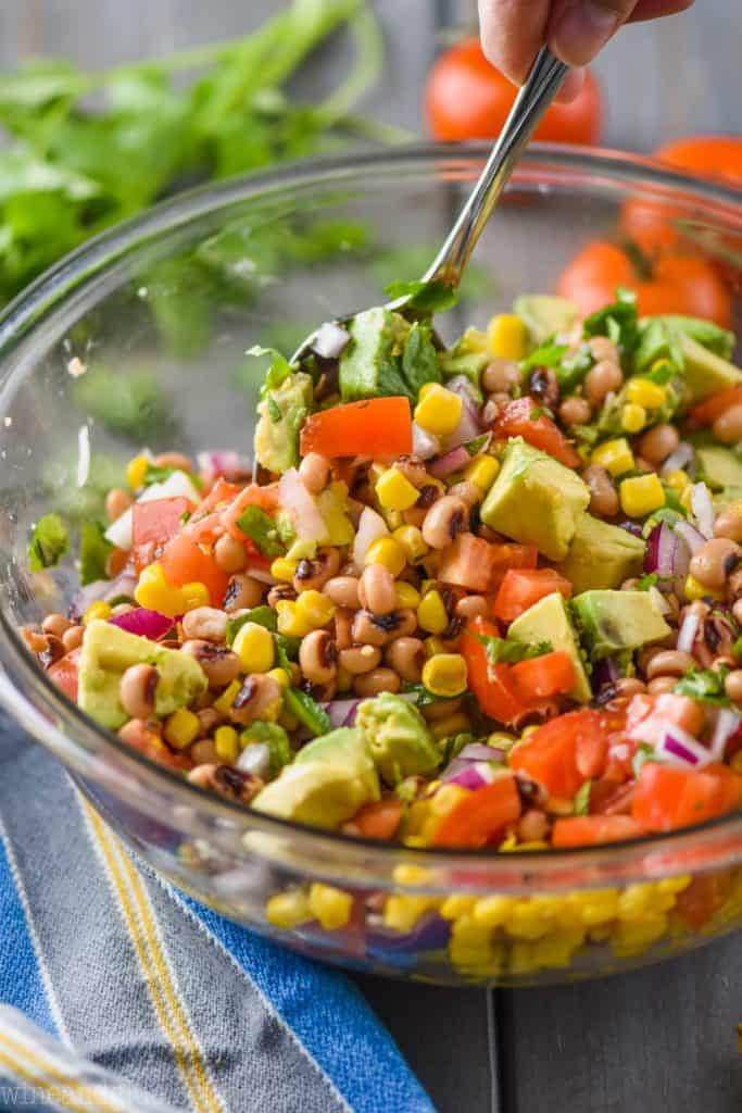 side view of a bowl of cowboy caviar with avocado being mixed up