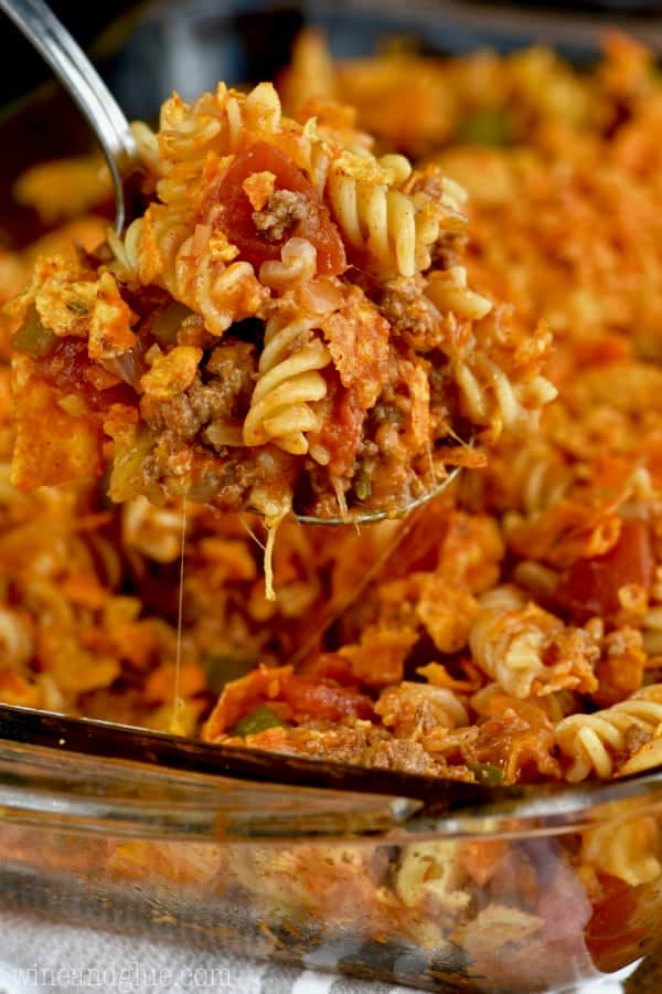 In a glass casserole dish, a spoon is digging into the Pasta Taco Casserole which has cheese stretching out of the dish