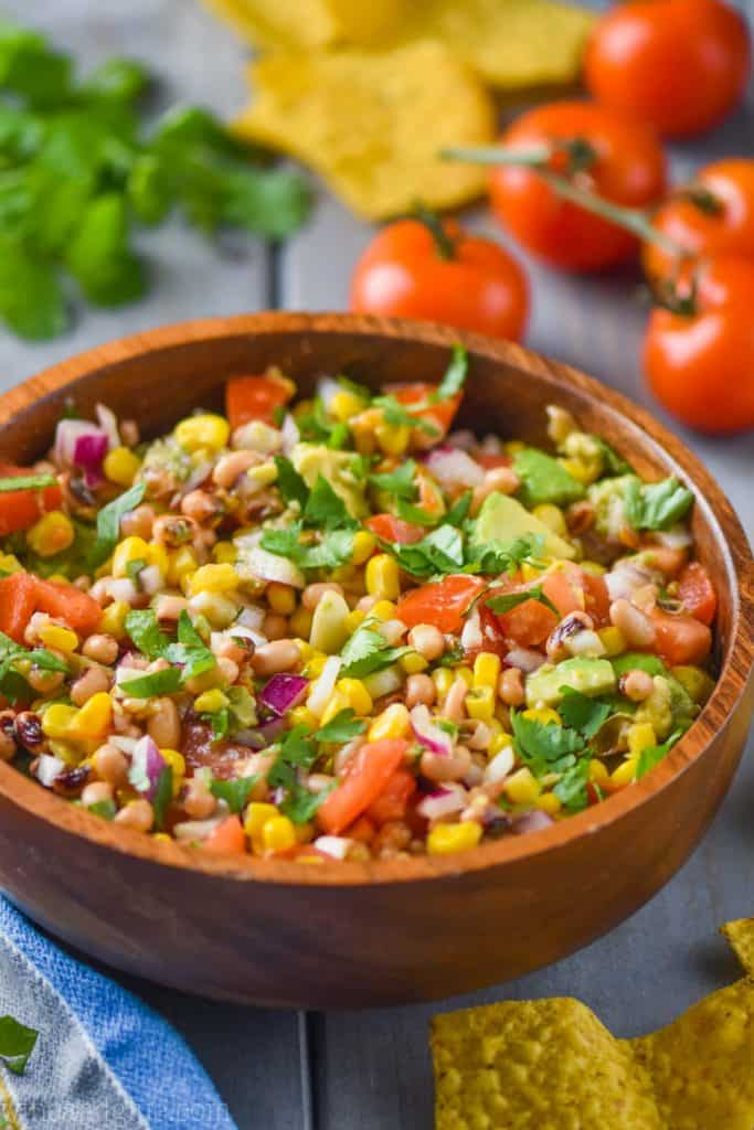 texas caviar in a wood bowl full of black eyed peas, cilantro, chopped up tomatoes, corn, and red onion