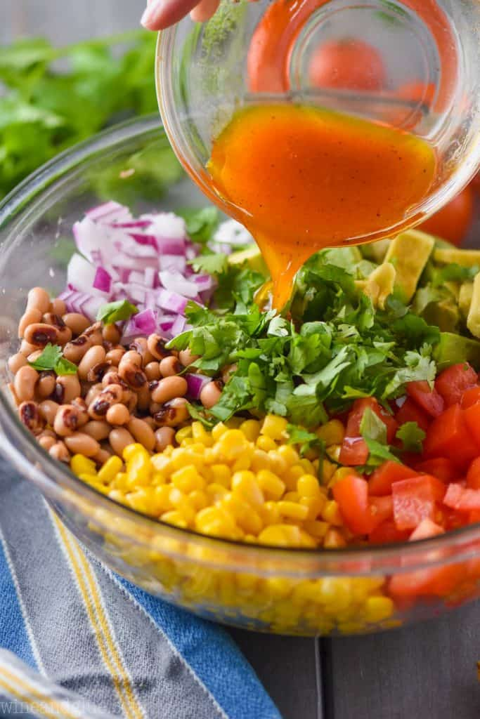 side view of a vinaigrette dressing being poured over a bowl full of ingredients to make cowboy caviar