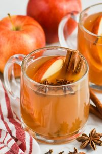 clear mug full of crockpot spiced apple cider with anise seed pods floating in it, apple slices and two cinnamon sticks