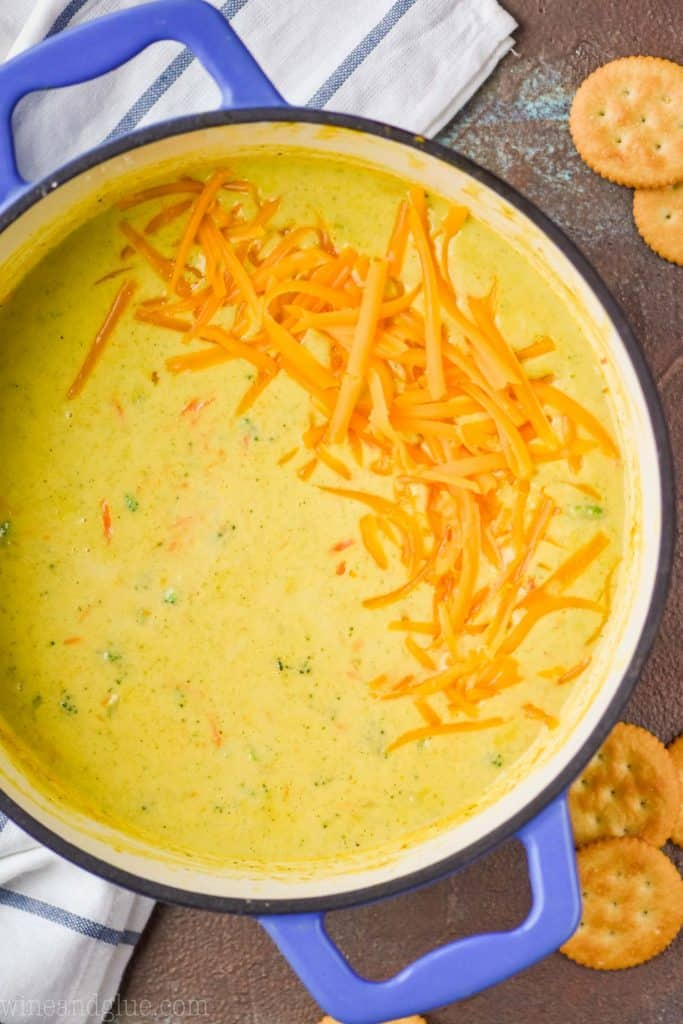 overhead view of a blue dutch oven full of Panera broccoli cheddar soup, garnished with more shredded cheese on a brown surface