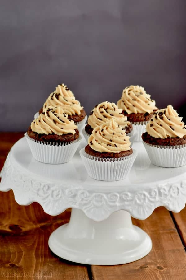 In white cupcake liners, are the Chocolate Peanut Butter Brownie Cupcakes topped with Peanut Butter frosting in a whipped shaped and chocolate sprinkles.