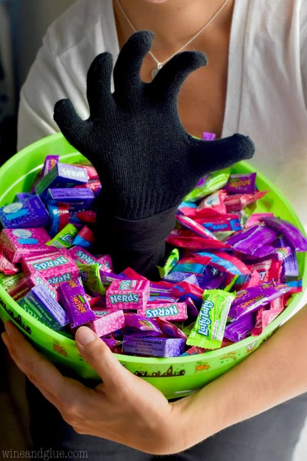 The Scary Halloween Treat Bucket with a hand coming out in a claw shape filled with candy.