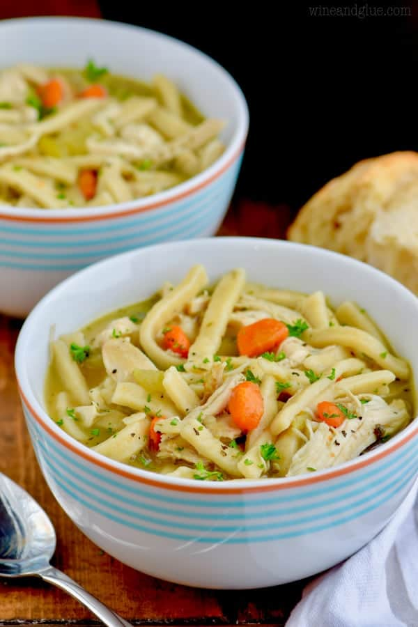In a white bowl with blue stripes, the Homemade Chicken Noodle Soup has thick noodles and topped with minced parsley.