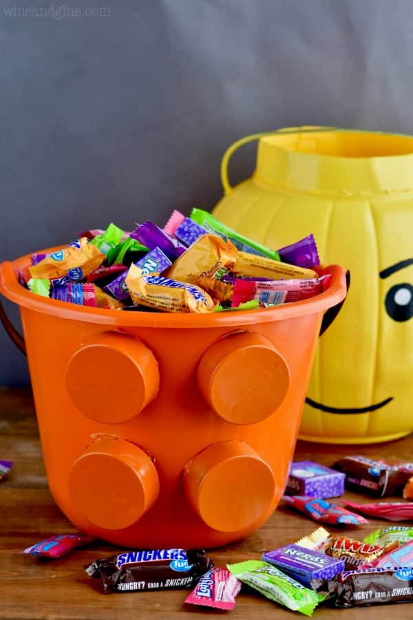 In the foreground, the lego piece bucket is filled with candy.