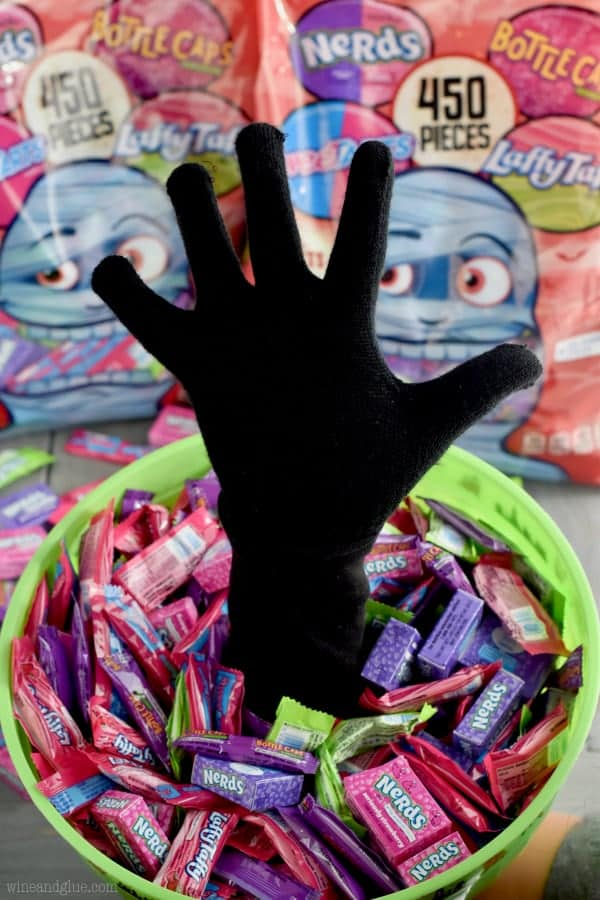 A bucket filled with Nerds and Laffy Taffy has a hand coming out of it.