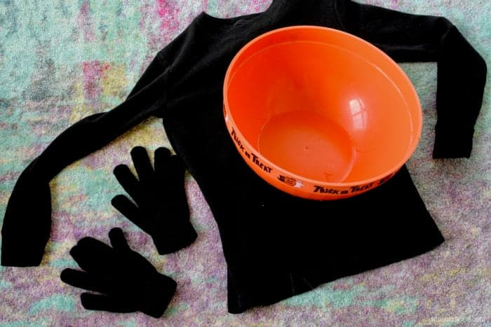 Two black gloves, a long black sleeves shirt, and a candy bowl are in the photo