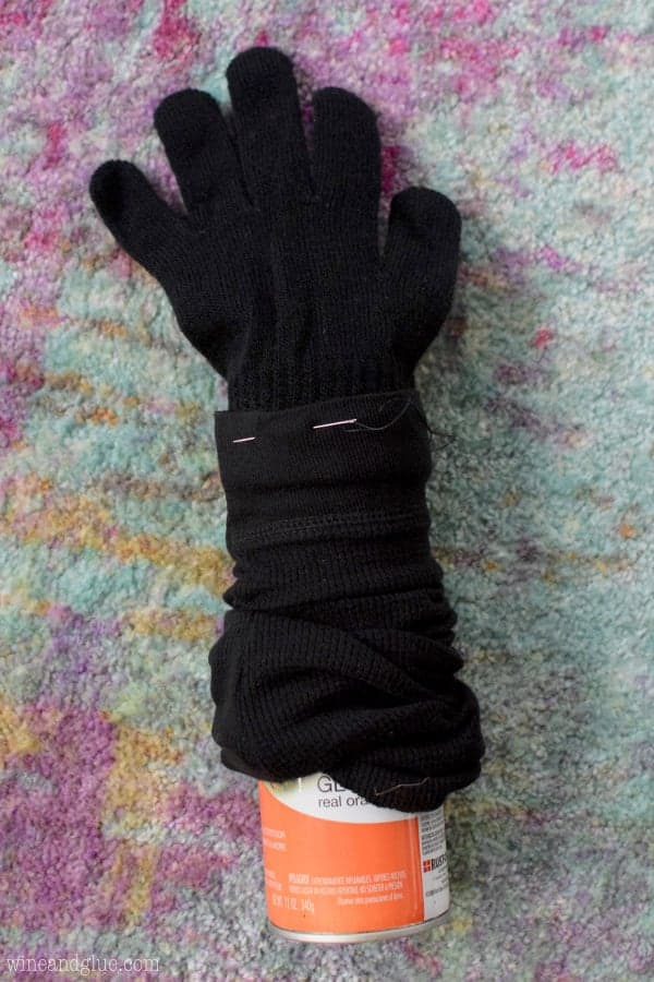 A sleeve from the black longed sleeved shirt has a black glove attached to it and a can on the other side.