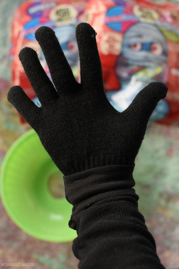 With the black glove attached to the sleeve, you wear the whole thing and place your hand through the whole into the bucket.